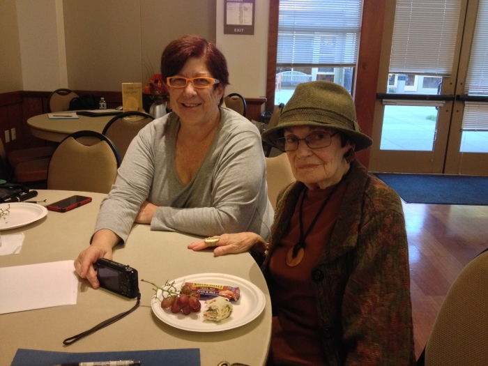TimeBank member Sena receives help with her camera from new member Helen.