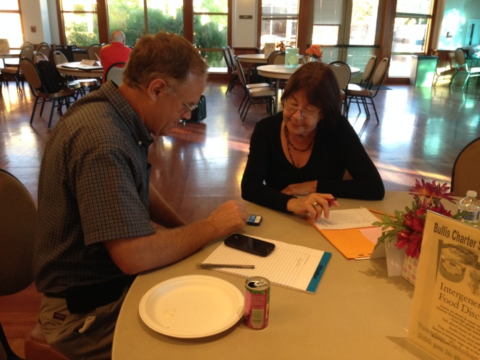 Mark, a longtime TimeBank member, shows new member Margarita how to use her iPhone 5s.